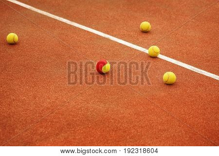Four yellow and one red-yellow tennis balls lie on the tennis court. The concept of sport. Be different.