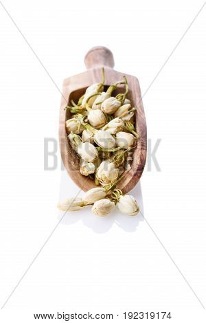 Close-up of dry jasmine flowers on wooden scoop. Healthy herbal tea Isolated on white background.