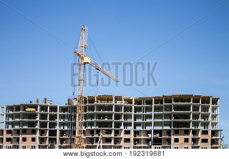 View from afar to a house under construction and a crane against a blue sky