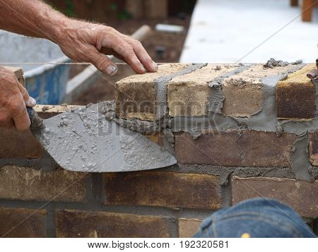 A brick mason uses a trolle to spread mortar and to clear away the excess.
