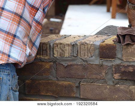 A brick mason prepares the level line for a second row of bricks being laid.