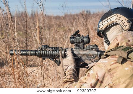 airsoft player in NATO uniform with rifle in ambush close up picture