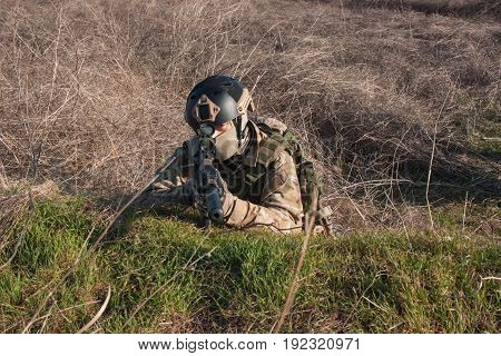 airsoft player in NATO uniform with rifle in ambush