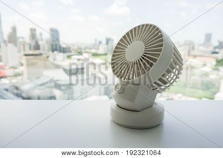 white portable USB desktop fan on office table to release hot air