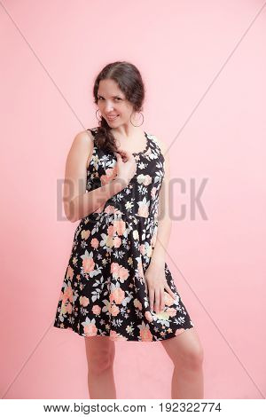 Portrait of a girl in a dress on a pink background