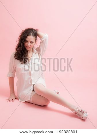 sensual girl in a white shirt on a pink background