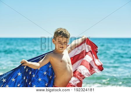 The boy with the flag of America on the sea shore