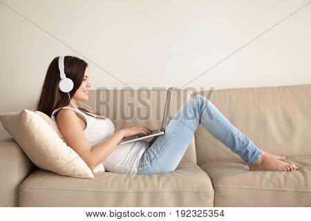 young woman in casual clothes and headphones lying on sofa and using laptop. Smiling teen girl listens and buying music in web store, watching online video, playing computer games at home