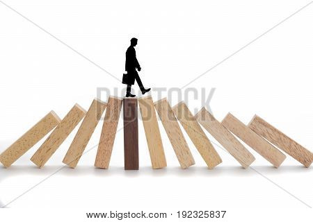 Business risks concept Businessman walking on wooden blocks.