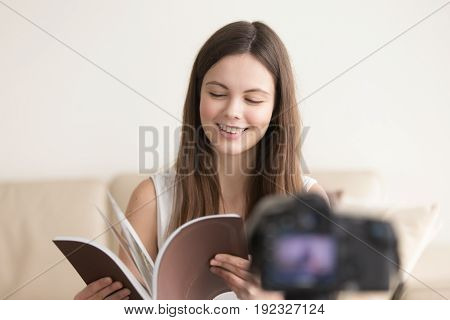 Young smiling woman sitting in front of video camera and reading book in hands. Teen girl recording her new book or products catalog video review. Female blogger makes vlog or live stream in Internet