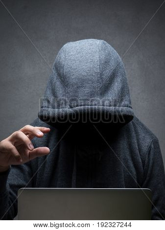 hacker wearing hood working with computer notebook