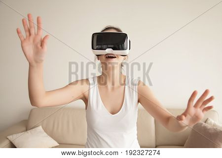 Young woman enjoys VR gaming on sofa at home. Lady excited first virtual reality experience, tries to touch objects in digital simulation app, playing computer games, shopping online with VR technology
