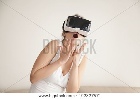 Young woman feels scared watching horror movie in VR glasses. Lady surprised with effect of presence in realistic digital simulation. Bright emotional reaction, using VR headset for the first time
