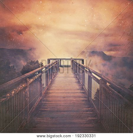 Atmospheric scene of a wooden bridge leading into low clouds and starry sky above misty mountains