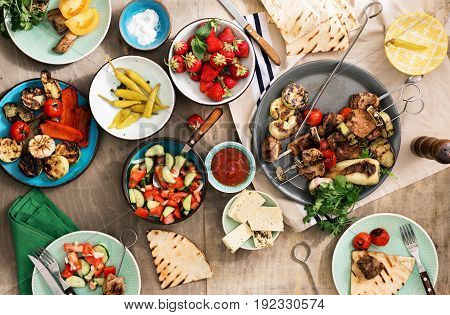 Different food cooking on the grill. Shish kebab grilled vegetables salad snacks and strawberries. Dinner table concept