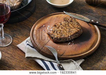 Beef rare grilled steak on wooden board with a glass of red wine