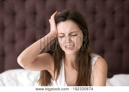 Young woman suffering from headache or migraine after wake up in morning. Stressed lady in bed with painful face expression feels terrible hangover, sharp pain in head, unpleasant weakness, dizziness