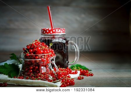 Ripe red currant and black currant juice on a wooden table. Summer still life.