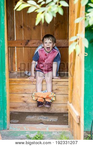 The child manages the need for a rustic toilet
