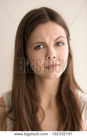 Headshot portrait of skeptic young woman. Beautiful teen girl with distrustful facial expression looking at camera with suspiciousness. Cute female feeling mistrust and doubt. Close up. Front view