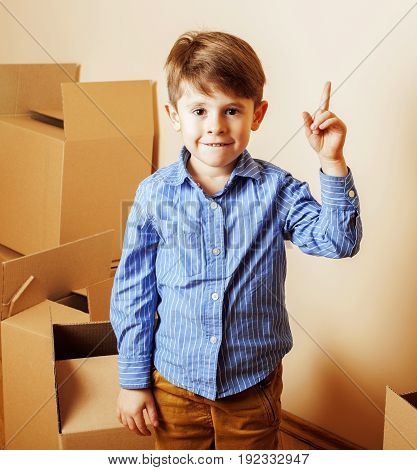 little cute boy in empty room, move to new house. home alone among boxes close up kid smiling, lifestyle real people concept