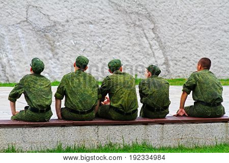 Back view of young army men sitting on a bench