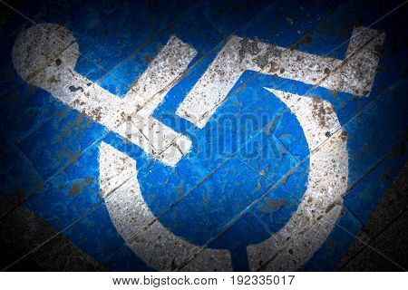 Disability symbol painted on the floor. Road sign.