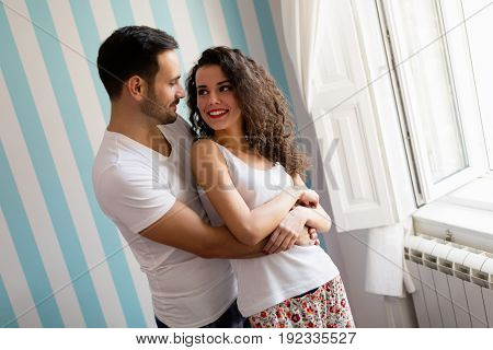 Handsome young man hugs beautiful woman with curly hair