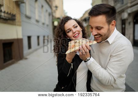 Happy young couple sharing one pizza cut on street