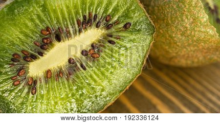 Two Kiwi Fruits sit on the cutting board on cut in half showing inside close up