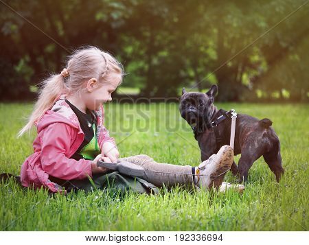 A child with a dog on a green lawn