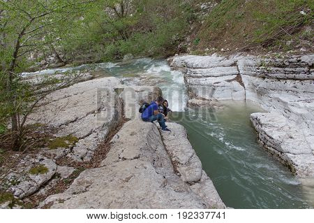 The beautiful canyon with turquoise pond and waterfall in the Mountains as the tourist walked along the trail. Traveler young girl and men walking in waterfall canyon. Active hikers
