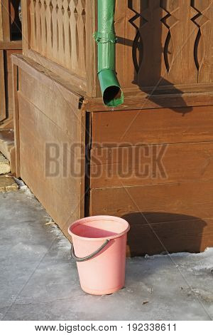 The supplied plastic bucket collects melt water from the downpour of the village house