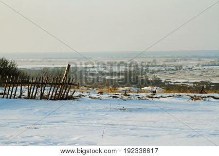 Old rickety fence against the background of a winter field in the horizon