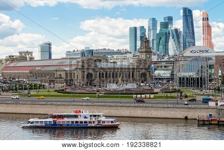 MOSCOW RUSSIA - JUNE 6 2017: Tourist boat on the Moscow river Kiev railway station Europe Square with skyscrapers international business center