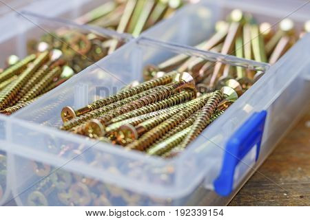Long Self-tapping Screws In Transparent Plastic Storage Box On A Wooden Bench