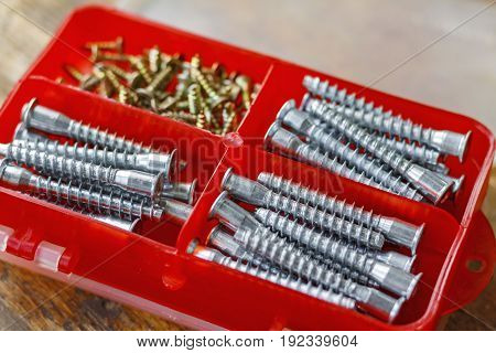 Set Of Fasteners For Assembling Furniture In A Red Plastic Storage Box On A Wooden Table