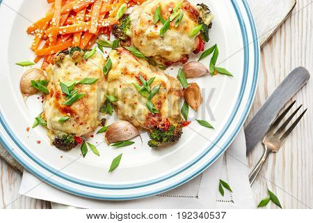 Roasted teriyaki chicken thighs  stuffed with vegetables, baked with mozzarella cheese on a white plate