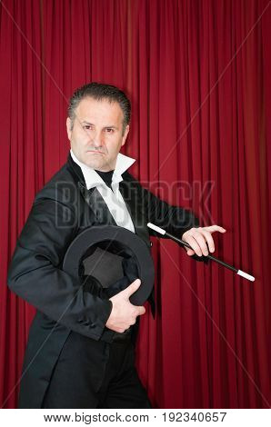Magician In Tuxedo On Stage, Color Image, Red Background