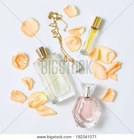 Perfume bottles with flowers petals on white background. Perfumery, cosmetics, jewelry and fragrance collection. Stylized feminine flatlay. Women accessories top view