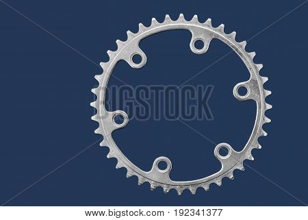 High contrast image of a leading chain-wheel for a bicycle on a dark-blue background.