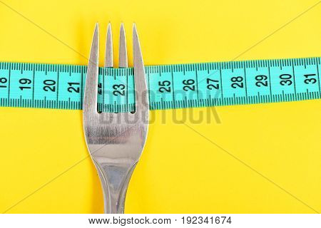 Fork In Silver Color With Four Tines Holding Measuring Tape