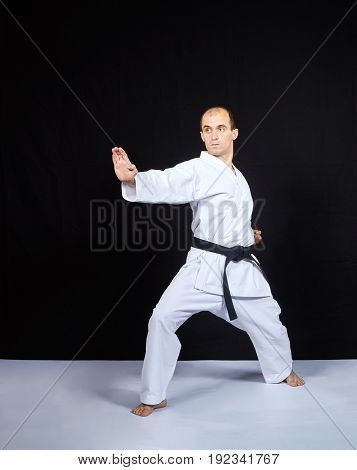 On a black background, an athlete in karategi trains a block with his hand