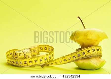 Metering of bitten apple with measure tape on light yellow background with copy space