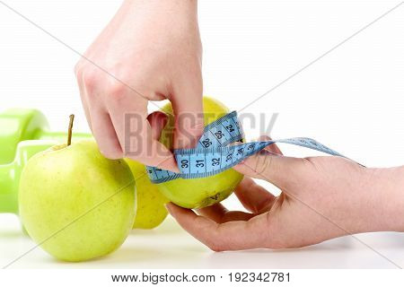 Hands Wrapping Blue Measuring Tape Around Green Apple