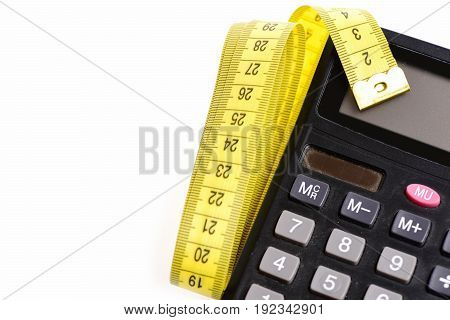 Calculating machine and neatly folded yellow measuring tape isolated on white background with copy space. Concept of counting and keeping fit