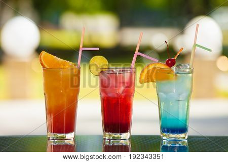 Three glasses of non-alcoholic drink and fruit on a table with a blurred background.
