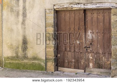 vintage Wooden door painted brown worn weathered on a country animal barn