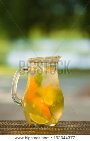 Jug of non-alcoholic drink and fruit on a table with a blurred background.