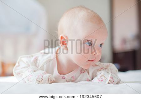 The  little baby girl crawls on the white bed
